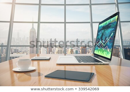 laptop and digital tablet with graph charts on wooden table stock photo © wavebreak_media