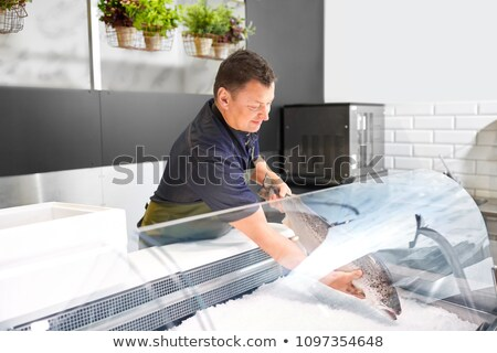 male seller putting trout to fridge at fish shop Stock photo © dolgachov