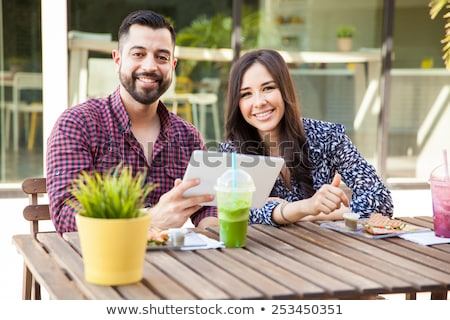Smiling couple using a tablet while sitting outdoors stock photo © Minervastock