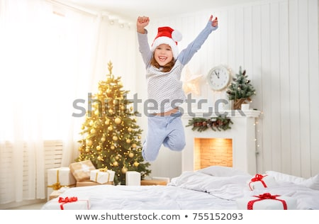 A happy funny child girl in bed on Christmas morning Stock photo © Lopolo
