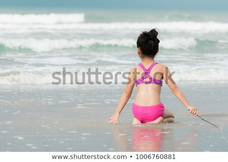 Little Girl Sitting In The Shallow Water At Beach Stock photo © AndreyPopov