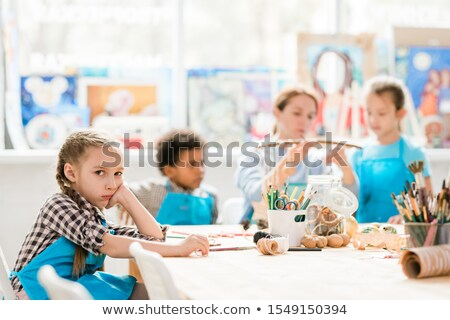 Cute unhappy schoolgirl looking at you while sitting by desk in front of camera Stock photo © pressmaster