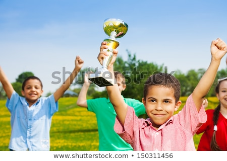 Little girl with the lifted hand is standing on grass field. long shadow on grass ground field. girl stock photo © Paha_L
