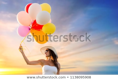 woman in sunglasses with balloons over sunset sky stock photo © dolgachov