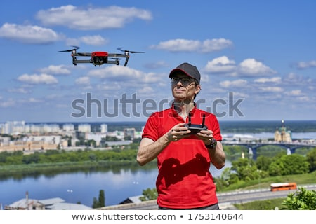 The man controls the drone against the background of the forest and the waterfall Stock photo © galitskaya
