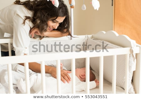 mother putting baby to sleep at the crib stock photo © lopolo