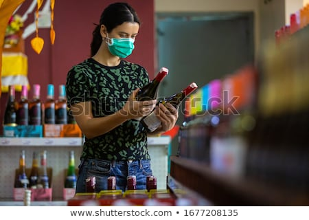Alarmed female wears medical mask against coronavirus while purchase of household chemicals in super Stock photo © galitskaya