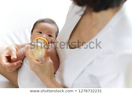 Young mother giving her baby a drinks bottle Stock photo © photography33