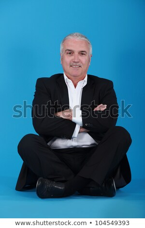 middle-aged man sitting cross-legged and cross-armed against blue background Stock photo © photography33