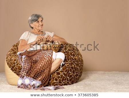 Portrait of a middle age woman knitting on spokes at home Stock photo © dashapetrenko