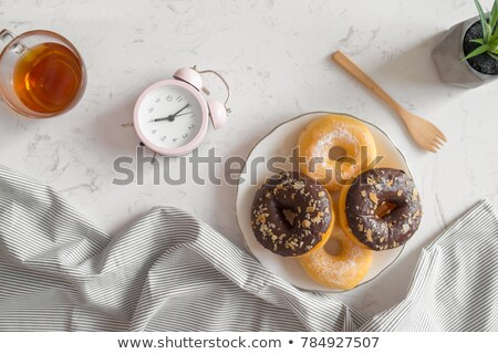 Sweet sugary donuts and vintage clock on rustic table Stock photo © stevanovicigor