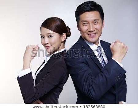 smiling asian business man woman back to back stock photo © qingwa