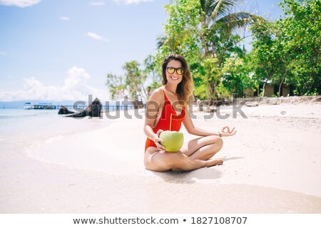 smiling woman meditating while sitting on sand stock photo © wavebreak_media