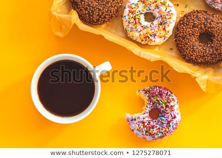 Stock photo: Delicious glazed donuts and cup of coffee on yellow surface