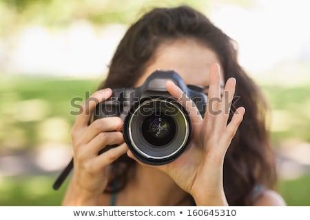beautiful brunette woman taking a picture outdoor by digital camera stock photo © artfotodima