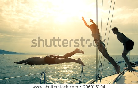 young woman jumping from a sailing boat stock photo © dashapetrenko