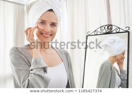 Smiling woman applying face cream wearing white robe in the morn Stock photo © dashapetrenko