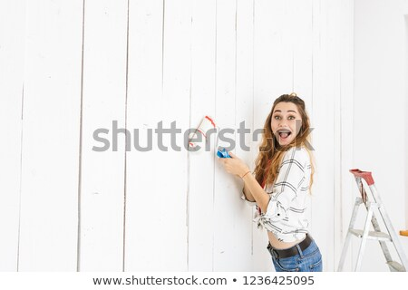 Image of beautiful woman 20s painting white wall and making reno Stock photo © deandrobot