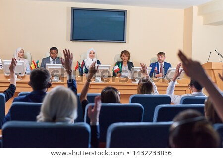 Audience in armchairs raising their hands to ask questions Stock photo © pressmaster
