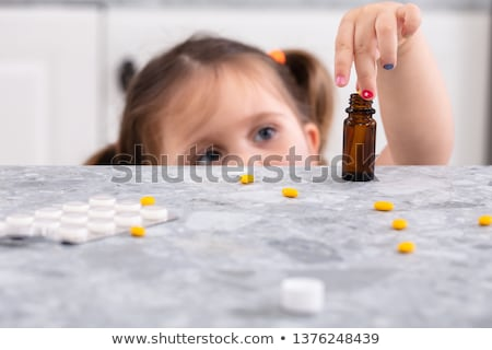 Girl Taking Tablets From Worktop Stock photo © AndreyPopov