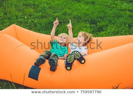 Two cute boys resting on an air sofa in the park. Stock photo © galitskaya