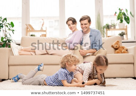 Two cute elementary age kids with touchpad lying on the floor of living-room Stock photo © pressmaster
