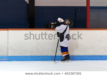 Hockey boy drinking water. Stock photo © iofoto