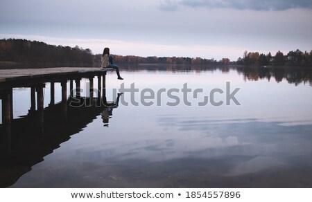 attractive woman resting at edge pier stock photo © elinamanninen