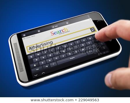 Pubblicità ricerca string smartphone dito pulsante Foto d'archivio © tashatuvango