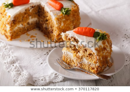 Fresh tasty sweet piece of  carrot cake on a white napkin and a dessert fork on a wooden background Stock photo © mcherevan