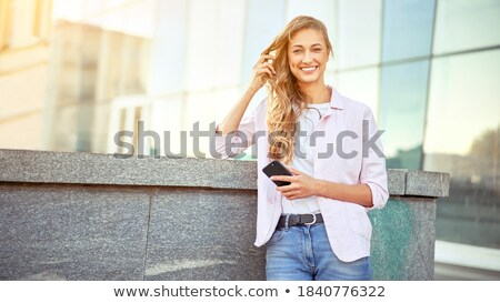 Enthusiastic female using phone outdoors Stock photo © dash
