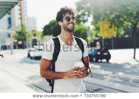 Happy young man student with backpack walking outdoors Stock photo © deandrobot