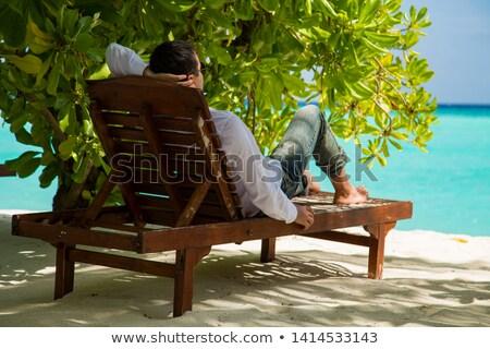 Młody człowiek posiedzenia ogród człowiek zabawy portret Zdjęcia stock © IS2