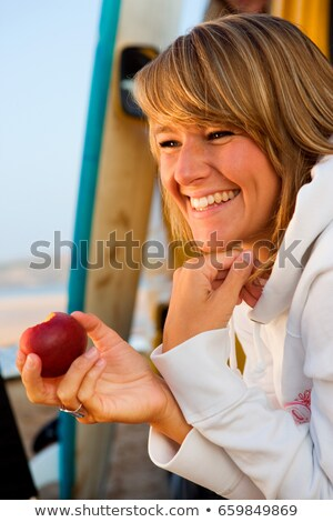 Woman eating an apple near surfboards Stock photo © IS2