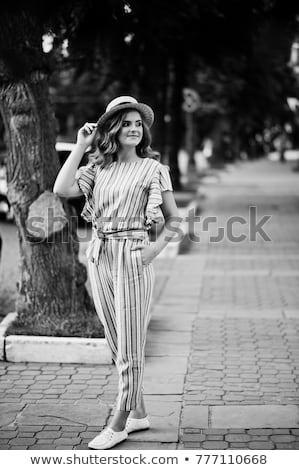Brunette in black and white striped overalls posing at street. stock photo © studiolucky