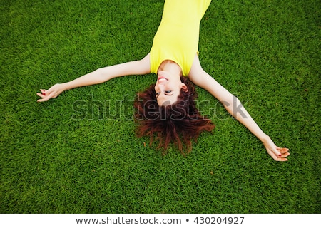 pretty young girl laying on grass at the park stock photo © deandrobot