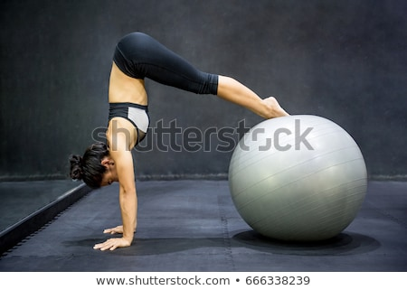 fit young woman practicing yoga on pilates ball stock photo © kzenon