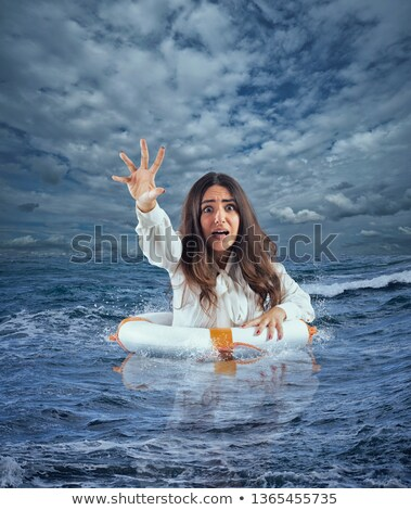 Businesswoman in the ocean with lifebelt asks help during a storm Stock photo © alphaspirit