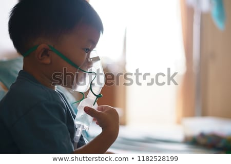 young boy using nebulizer for asthma and respiratory diseases at home teenager doing inhalation inh stock photo © elenabatkova