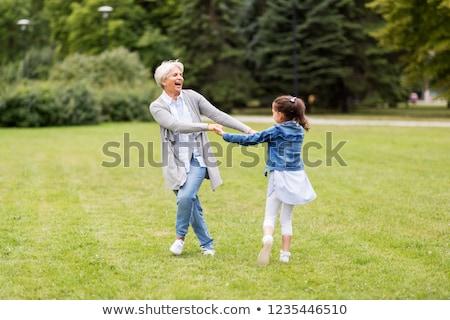 grandmother and granddaughter playing at park stock photo © dolgachov