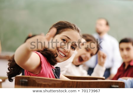 Pupils and teacher in class room of school showing thumbs-up Stock photo © Kzenon