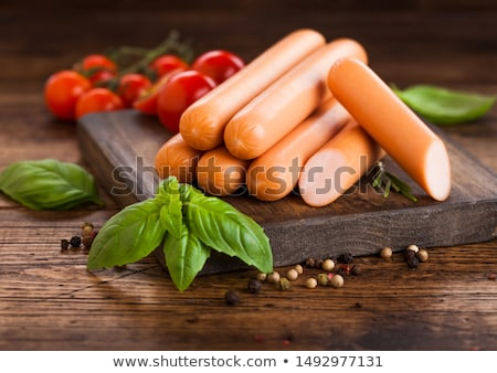 Classic boiled meat pork sausages with pepper and basil and cherry tomatoes on white background.  Stock photo © DenisMArt