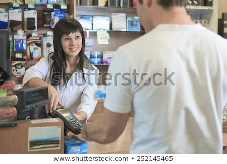 Pharmacist helping customer at counter place Stock photo © Lopolo