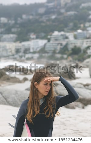 Front view of caucasian woman standing with surfboard shielding eyes at beach Stock photo © wavebreak_media