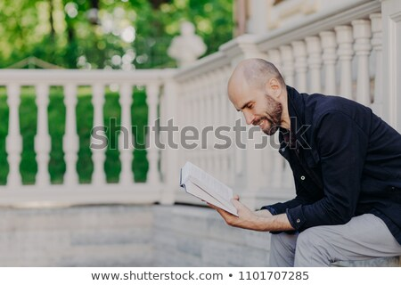 Photo of middle aged bald bearded man leans closely to book, has positive expression, sits against w Stock photo © vkstudio