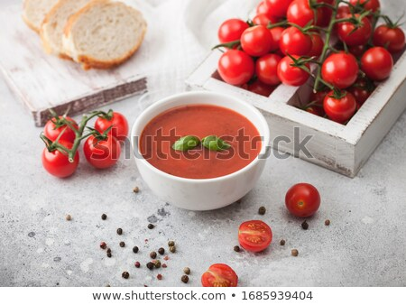 White bowl plate of creamy tomato soup with pepper on light table background with box of raw tomatoe Stock photo © DenisMArt