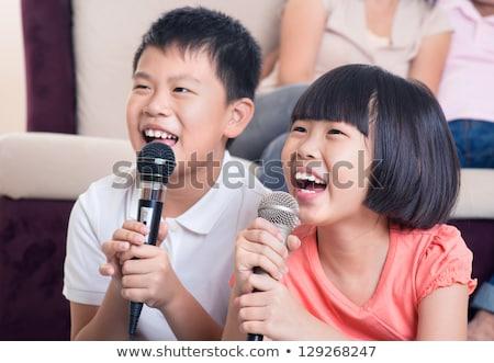 Kicsi énekes fiú énekel mikrofon bőrdzseki Stock fotó © Photoline