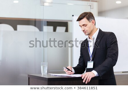 Confident handsome teacher standing at tribune and lecturing for students  Stock photo © deandrobot