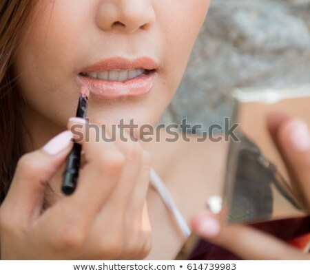 attractive happy woman applying red lipstick on part of lip stock photo © deandrobot