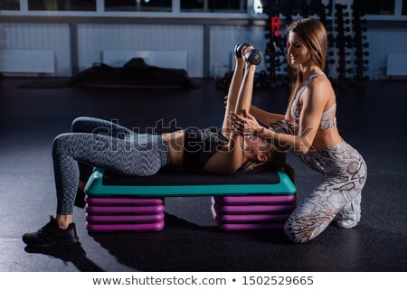 Young woman holding dumbbells in gym Stock photo © chesterf